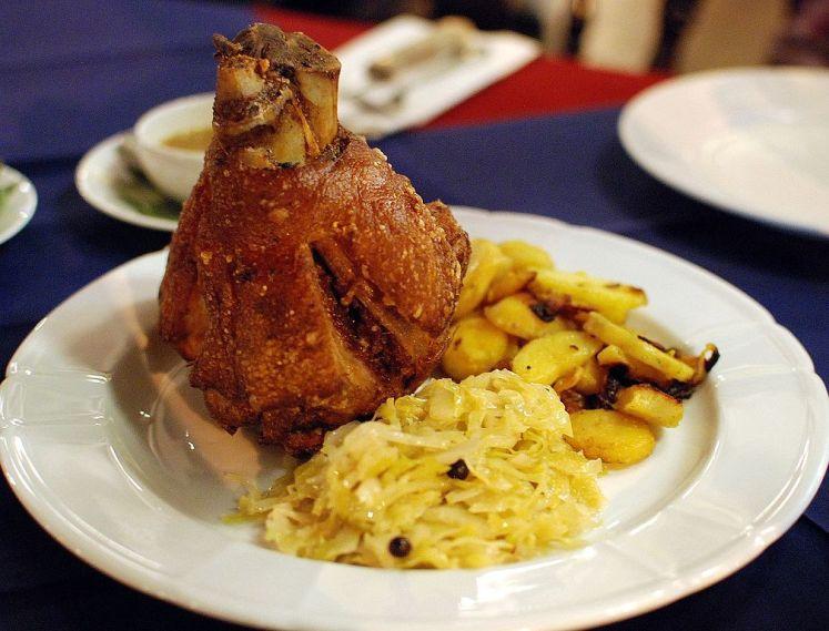 Bavorský grilované vepřové koleno podávané společně s brambory pečenými s cibulí a zelím.