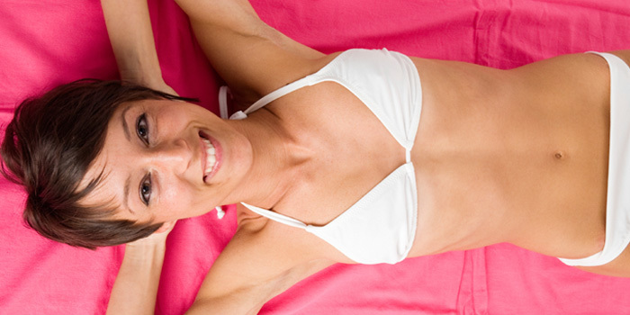 woman with flat stomach lying on blanket