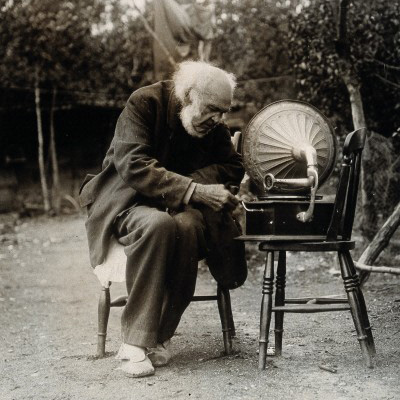 This photograph shows an old man sitting on a wooden chair outdoors, winding the handle of a gramophone player.