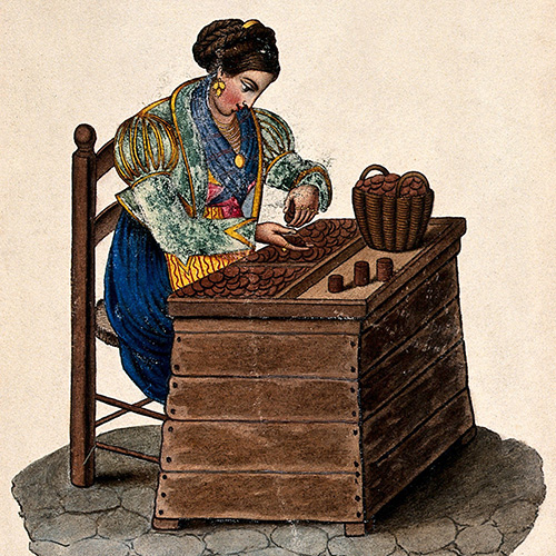 In this image a woman sits at a wooden box counting money out of a basket onto a tray.