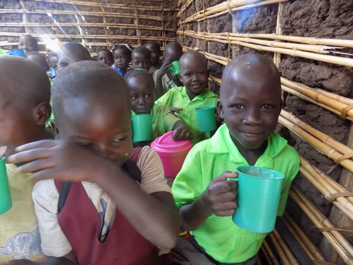 Ugandan school children holding green plastic cups filled with poridge