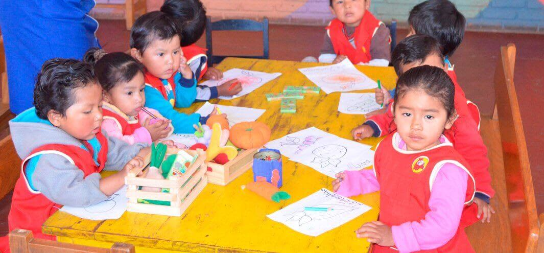 Bolivian children sit around a table at an Early Childhood Education Centre