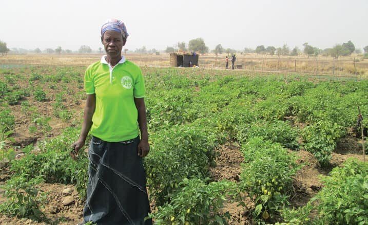 Ghanan women stands in her garden