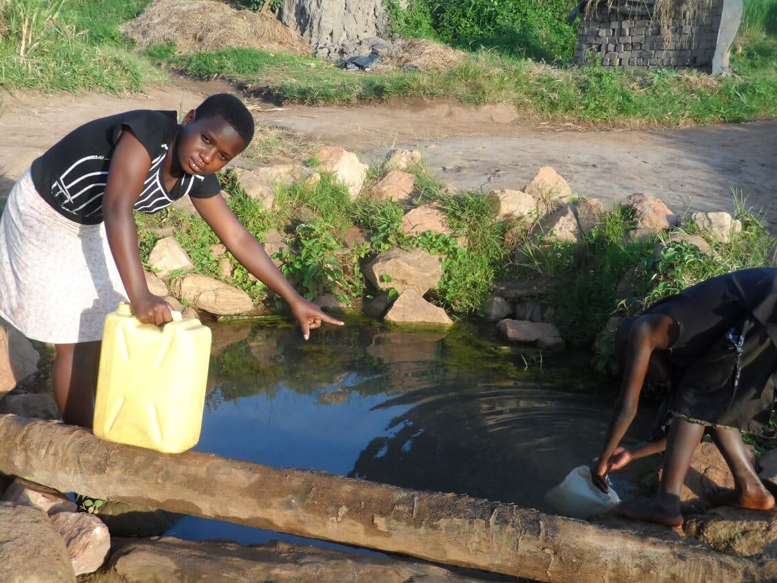 three african women collect water from a community well in Uganda