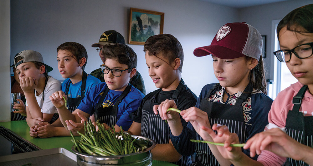 Canadian First Nations children in a kitchen trying asparagus
