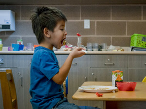 Indigenous Canadian boy eating lunch in his kitchen