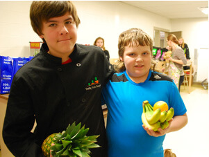 Two boys holding fruit, standing arm in arm