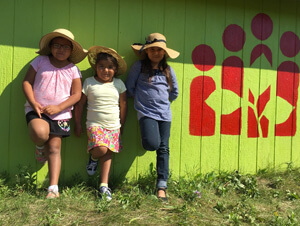 Three indigenous Canadian girls standing by a green wall with a CFTC logo painted on it