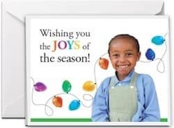 Donations as Gifts includes a free Christmas Card with a smiling African girl on the front with Christmas lights behind her.