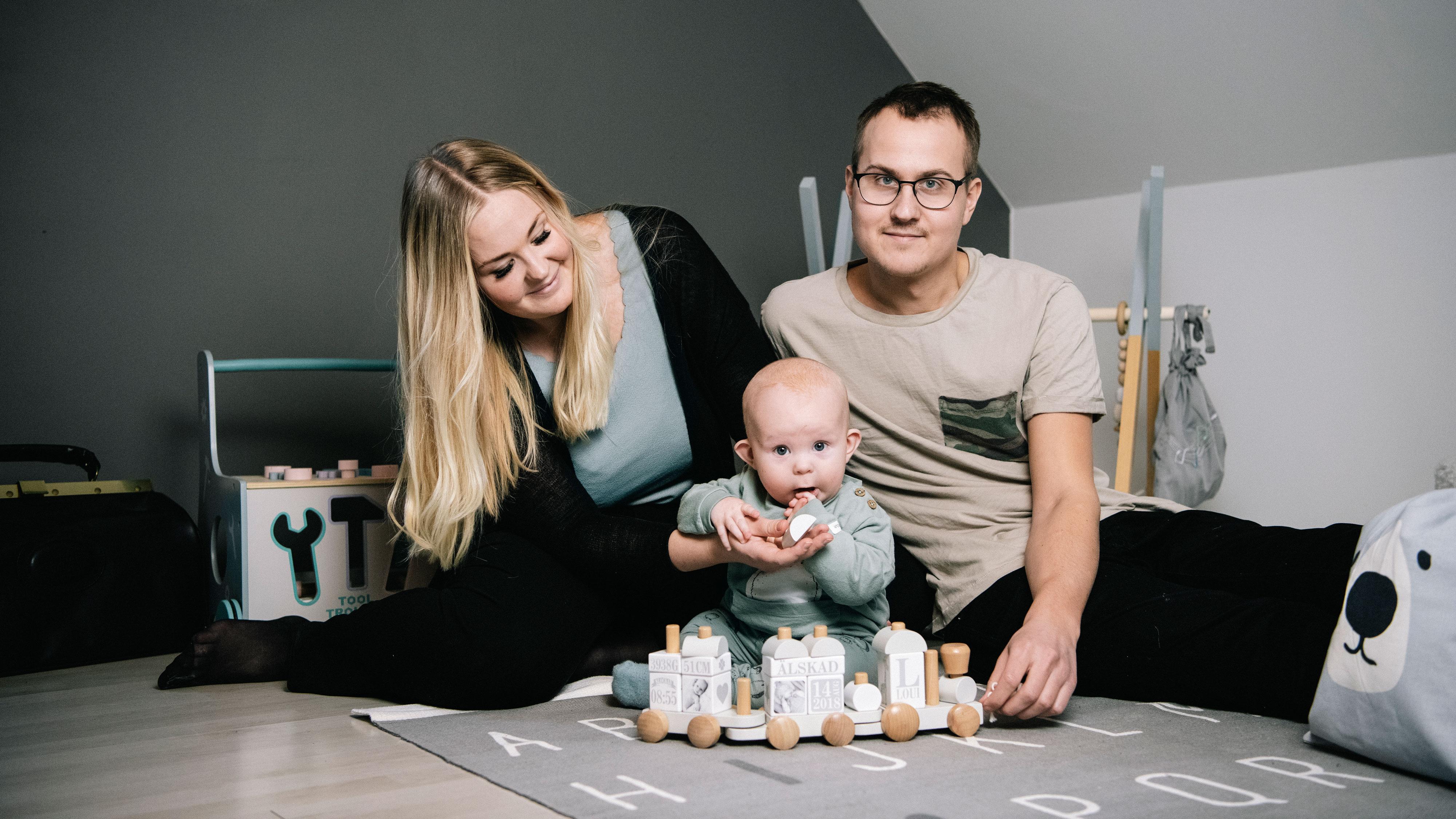 Marcus och Therése med deras son Loui på golvet med massa leksaker