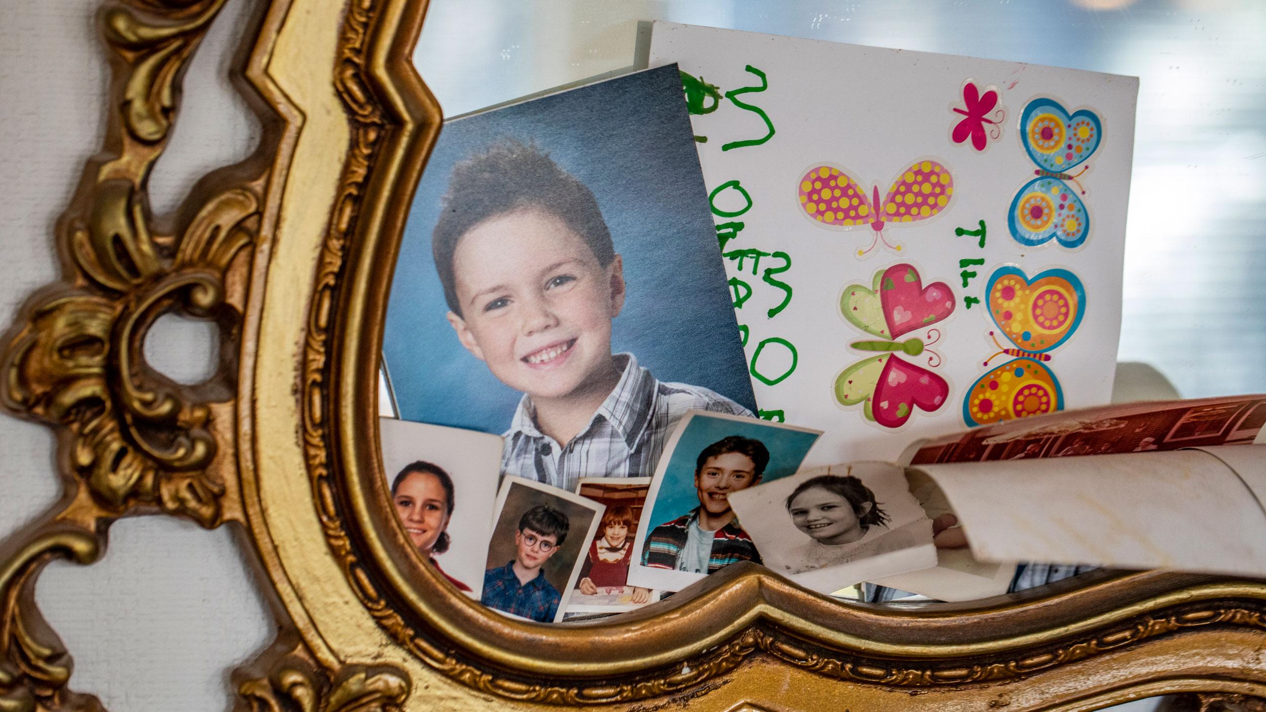 En guldig spegel där bilder på Göstas barnbarn är uppsatta.