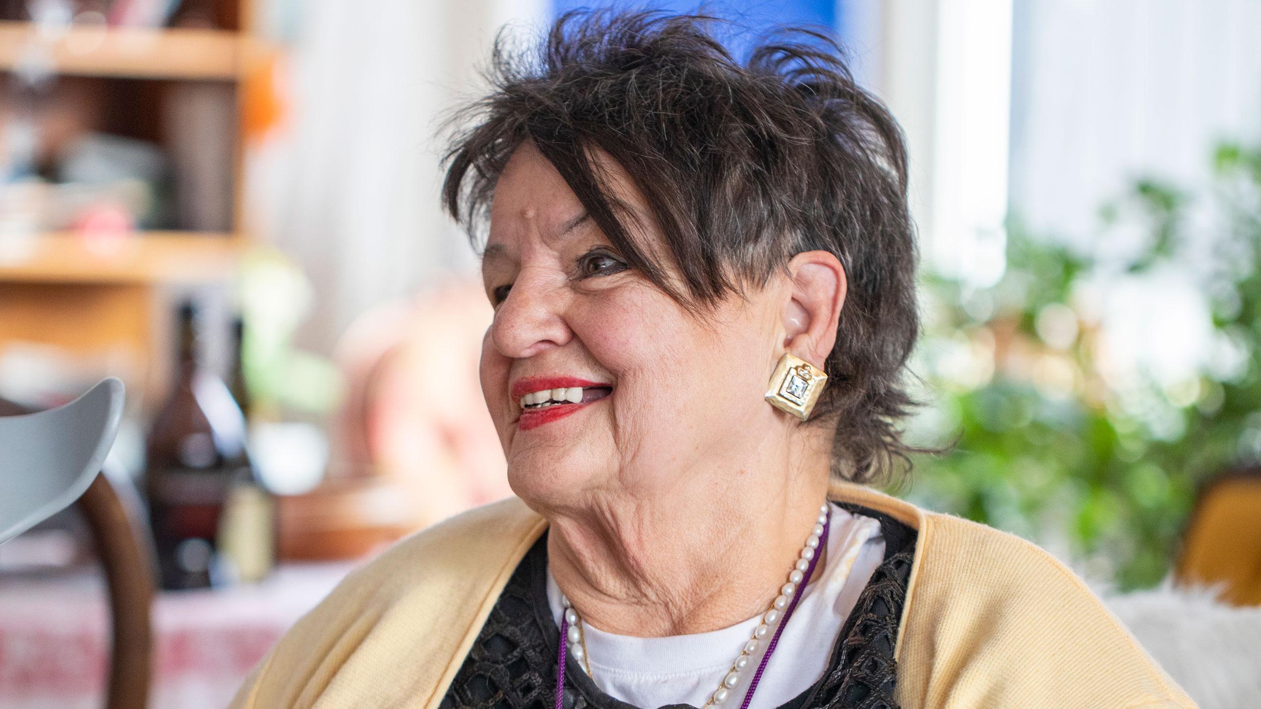 En äldre mörkhårig kvinna som sitter i profil.