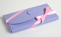 """Σοκολάτα διαστάσεων 10 Χ 5 εκατοστών, σε χάρτινη συσκευασία τύπου """"πεταλούδα"""" (η κατασκευή κλείνει με χάρτινο κοπτικό που θυμίζει φτερά πεταλούδας)"""