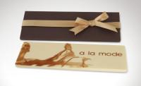 Σοκολάτα διαστάσεων 18 x 7 εκατοστών, σε χάρτινη συσκευασία. Για ποσότητες άνω των 200 τεμαχίων μπορεί να τυπωθεί και η συσκευασία. Υπάρχει η δυνατότητα διακόσμησης με κορδέλα.