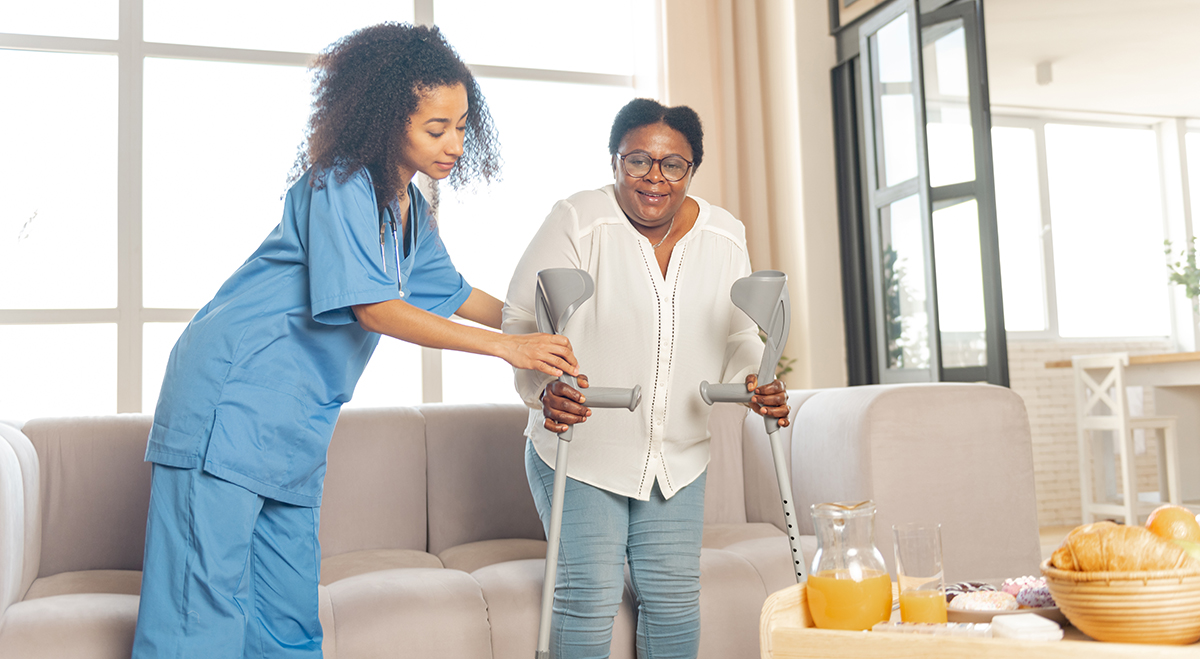 Nurse helping senior use crutches inside her home