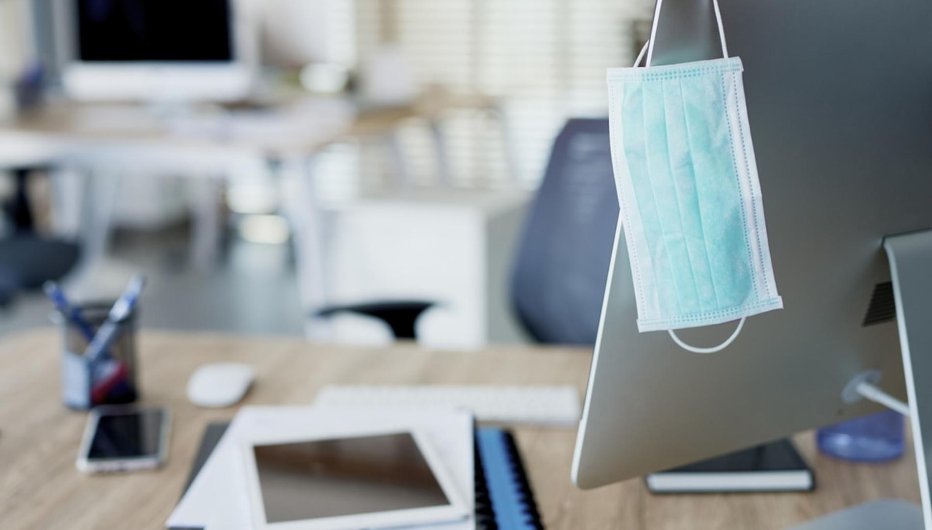 办公室里苹果电脑的一角挂着口罩.