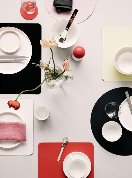 Kontrastreich: Weißes Porzellan trifft auf Platzteller aus italienischem Lederfaserstoff in kräftigen Farben.