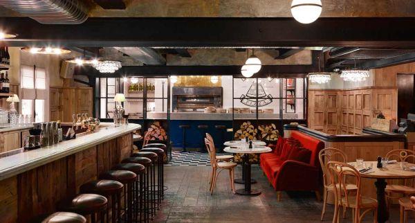 Im ersten Stock installierte die Designerin einen Pizzatresen und eine Cocktailbar. Viel Holz und die Ochre-Lampen sorgen für eine stimmungsvolle Atmosphäre.