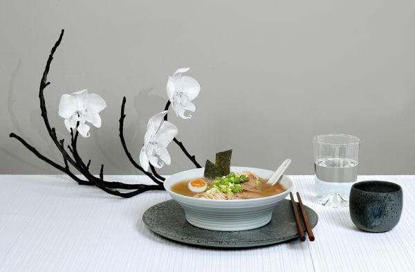 Die Schale greift die Rippen der Tischdecke auf (beides von Hering Berlin). Dazu Keramikteller und -becher von Würtz und ein Glas von New Tendency. Orchideenzweig aus Porzellan von Nymphenburg.