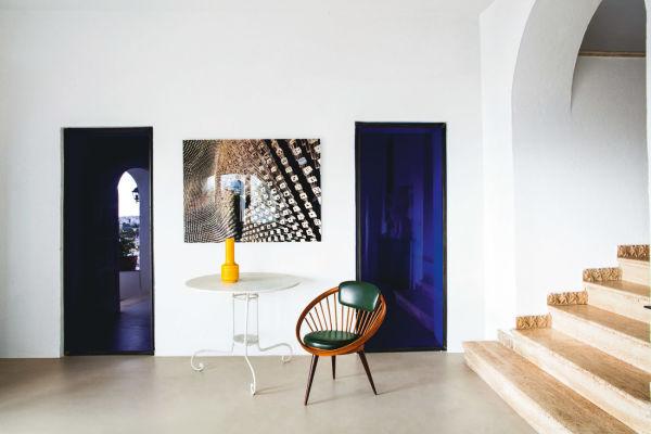 Kloster trifft Moderne: Vom Eingang führen blaue Glastüren in  Küche und Bad, dazwischen eine Fotoarbeit von Luciano Romano.