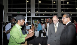 Jean-Sebastien Duvilaire: Haitian Jean-Sebastien Duvilaire, left, of Tahomey shows off one of his products to Secretary General of CARICOM, Irwin LaRocque, centre, and Premier of the Cayman Islands, Alden McLaughlin at Caribbean Week of Agriculture 2016