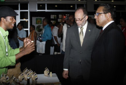 Haitian Jean-Sebastien Duvilaire, left, of Tahomey shows off one of his products to Secretary General of CARICOM, Irwin LaRocque, centre, and Premier of the Cayman Islands, Alden McLaughlin at Caribbean Week of Agriculture 2016 Agriculture MarketPlace in Grand Cayman on Oct. 26. (Photo: Kenton X. Chance)