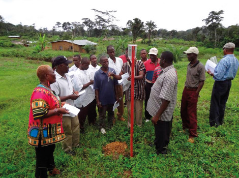 Villagers in Liberia being trained on how to use plastic rain gauges to measure rainfall © WMO