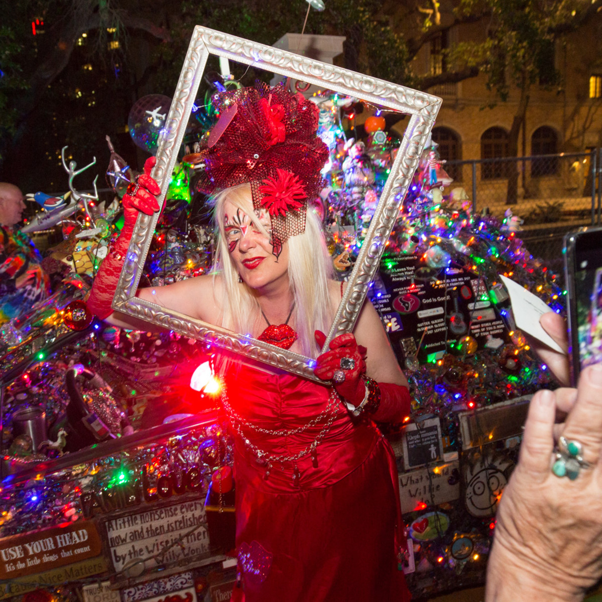 "Patti Paulson of Minnesota, owner of the ""Lipstick Car"" has her picture taken in a frame during the Legendary Art Car Ball"