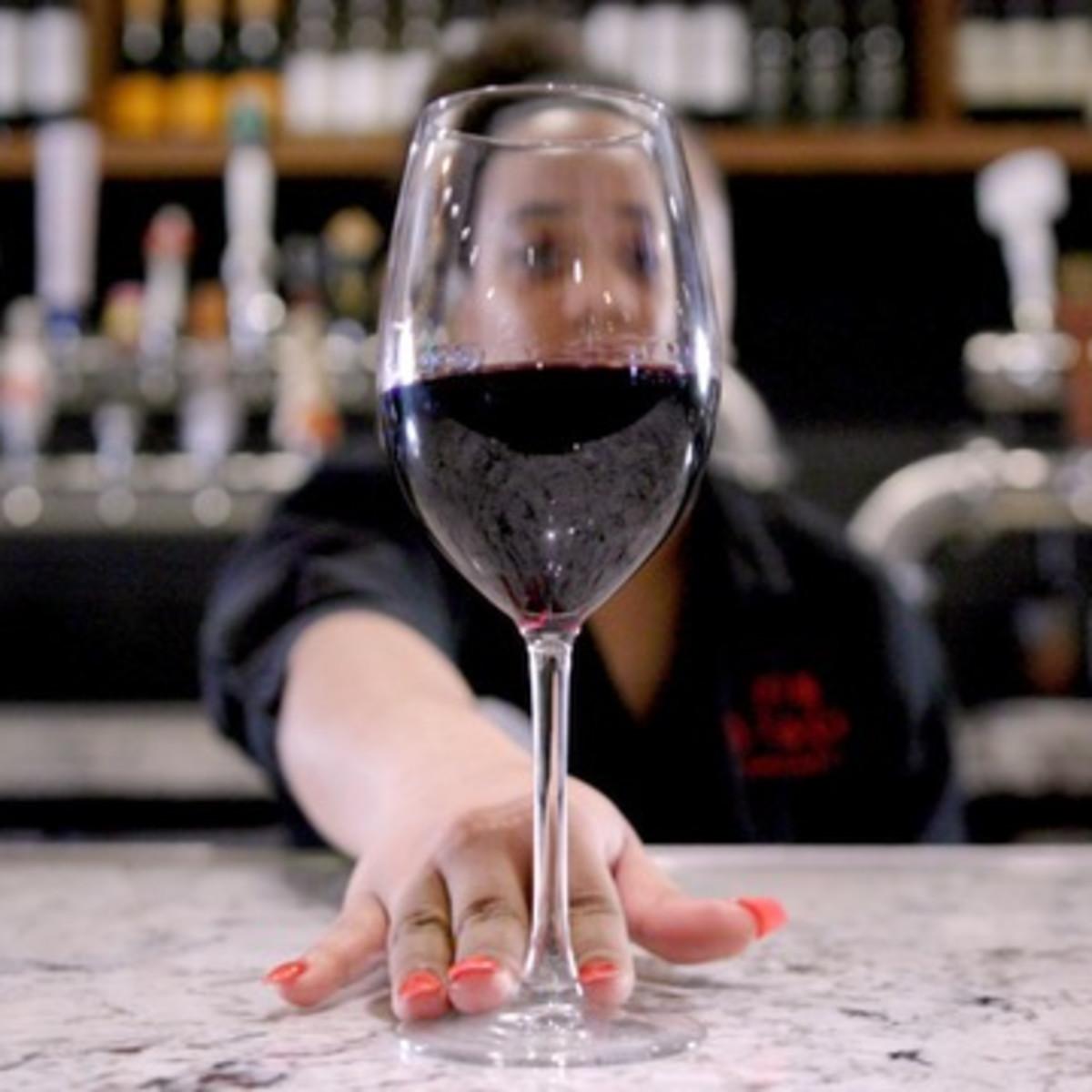 Bartender serving glass of wine