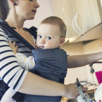 Mom washing dishes while holding her baby