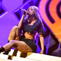 Cardi B singing sitting mic perform