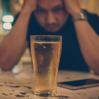 Man alone at bar drinking beer