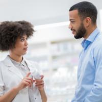 Pharmacist talking to man