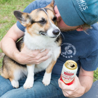 Man hugging dog while holding Austin Eastciders can