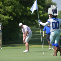 Men playing golf with Rowdy mascot