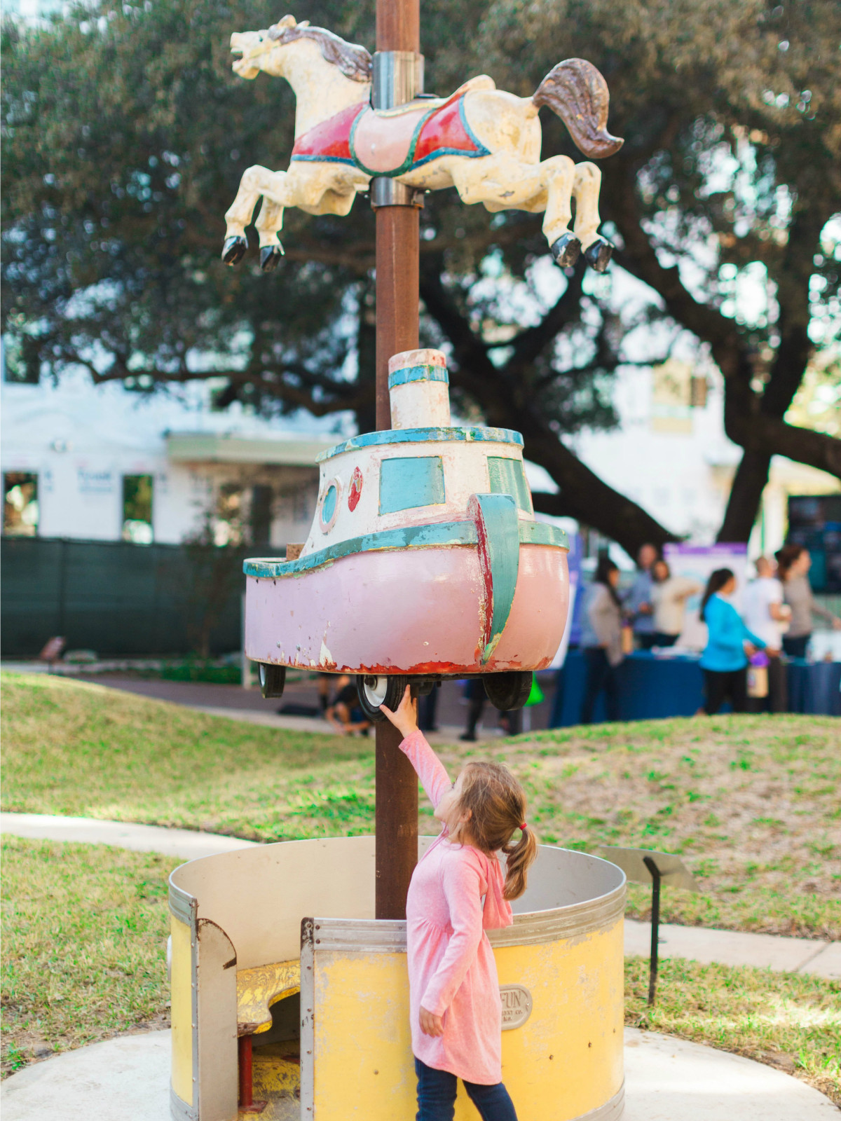 Little girl pointing at a carousel sculpture