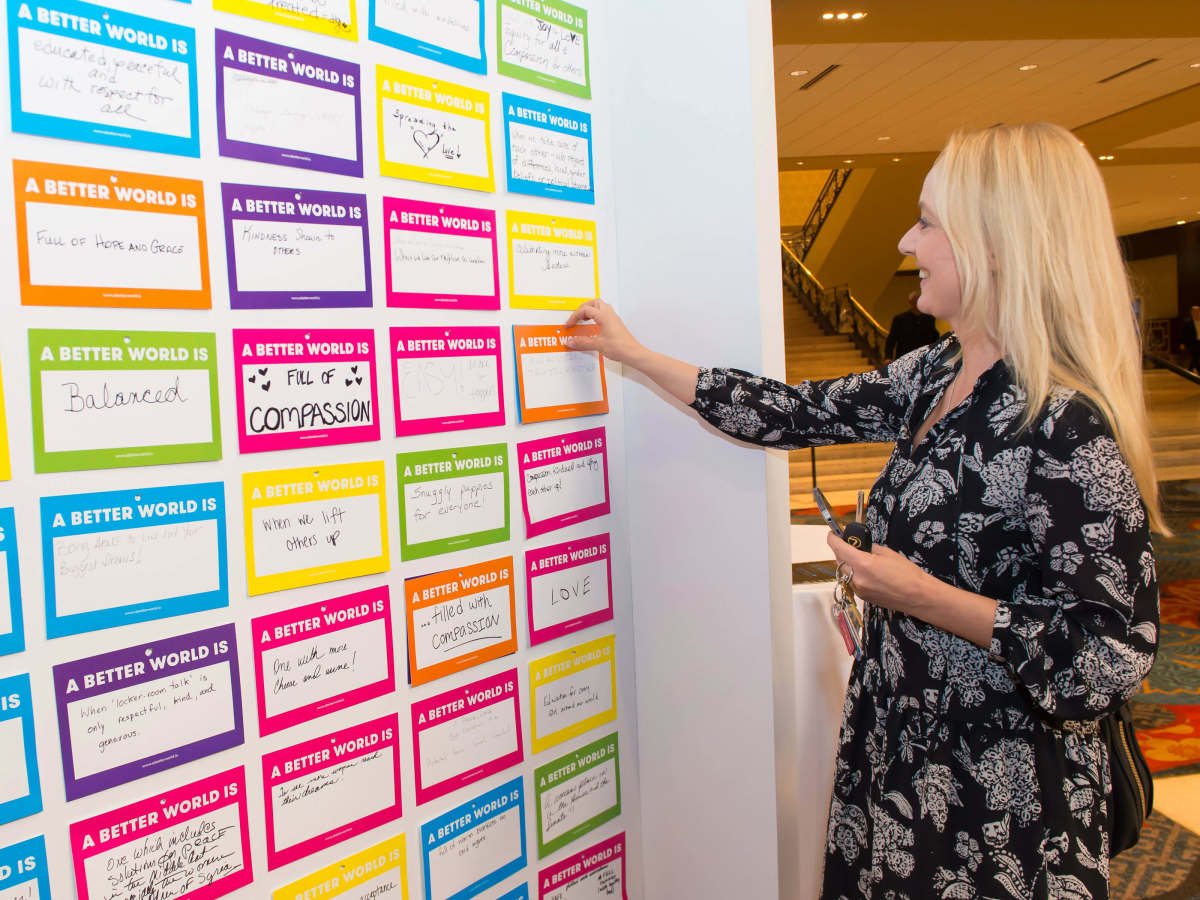 An attendee participates in the A Better World Is wall