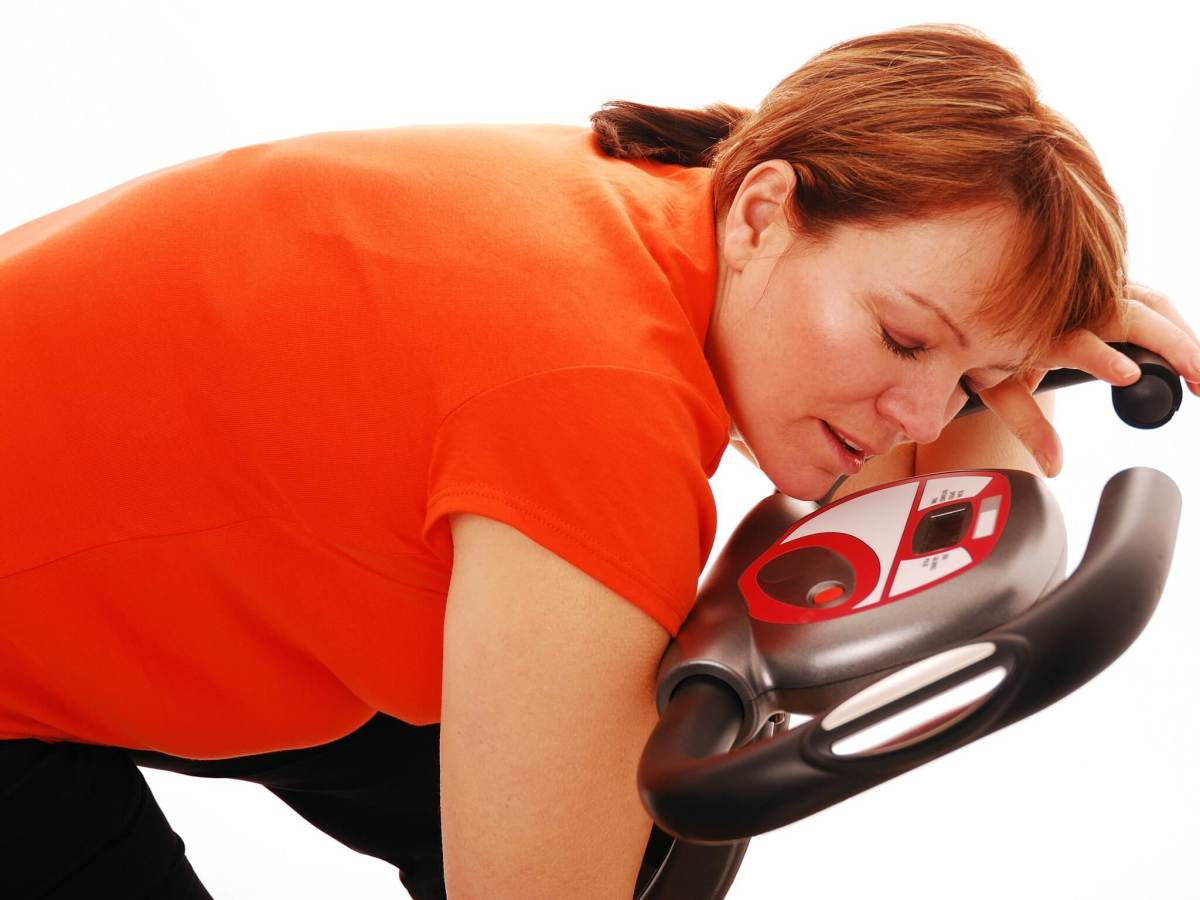 Exercise, fitness, woman asleep on the bike