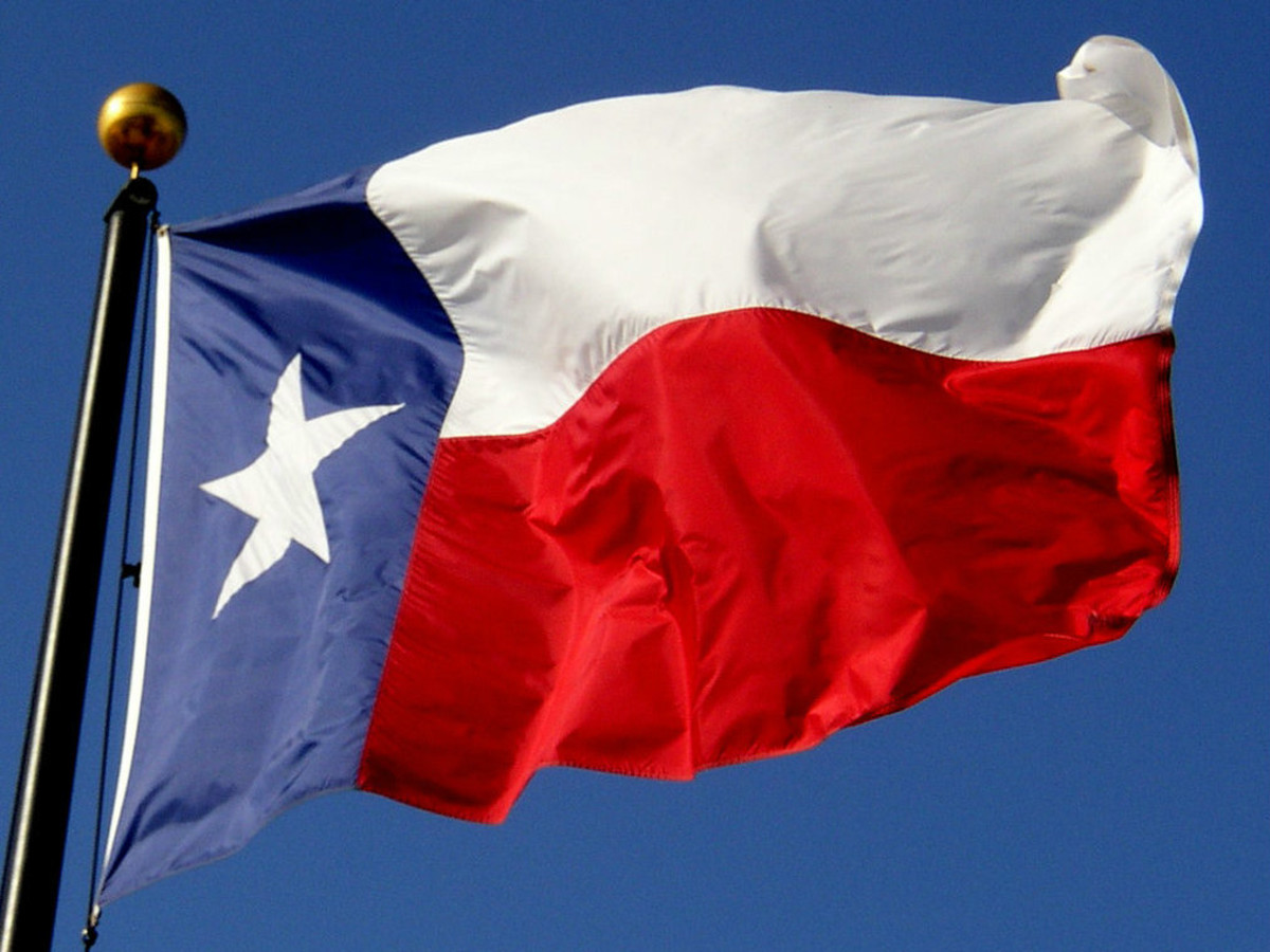 Texas flag flying with blue sky in background