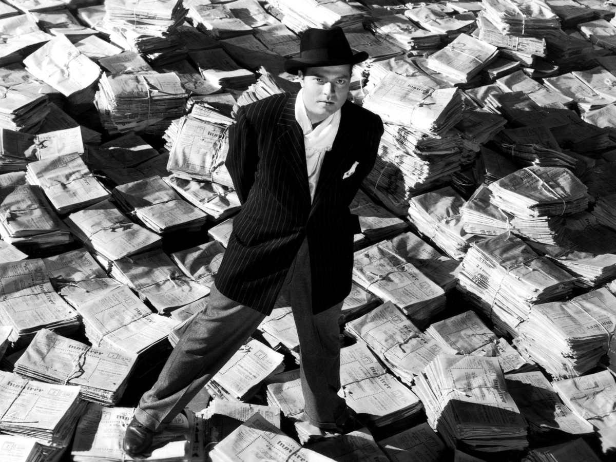 Orson Welles standing on mound of newspapers to promote Citizen Kane