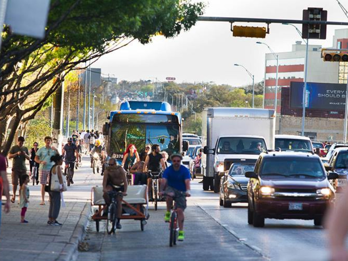 Cap metro bus cyclist busy downtown Austin street