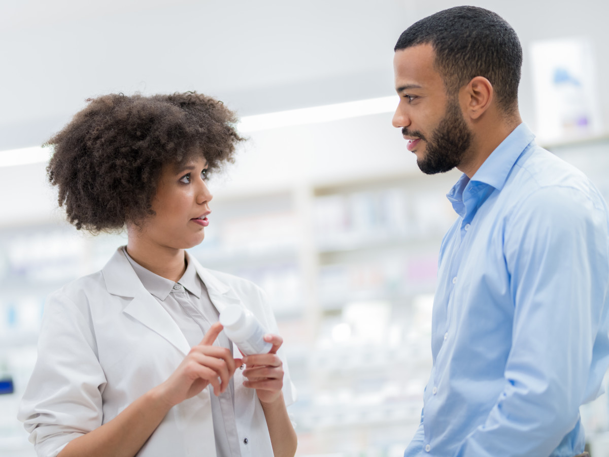 Pharmacist talking to man