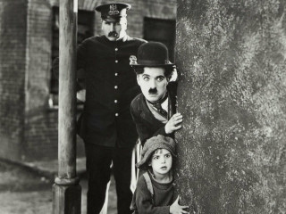 Charlie Chaplin with kid and police in the film The Kid