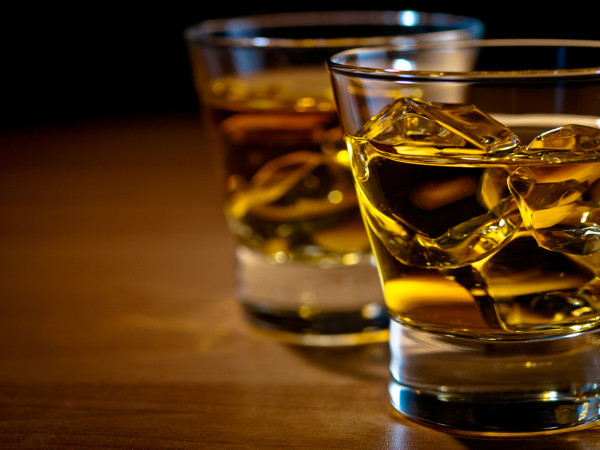 Glasses of whiskey with ice on bar or table