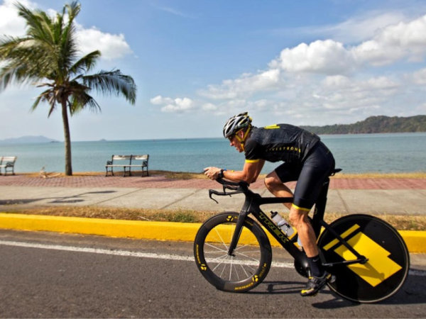 Lance Armstrong riding his bike along the beach