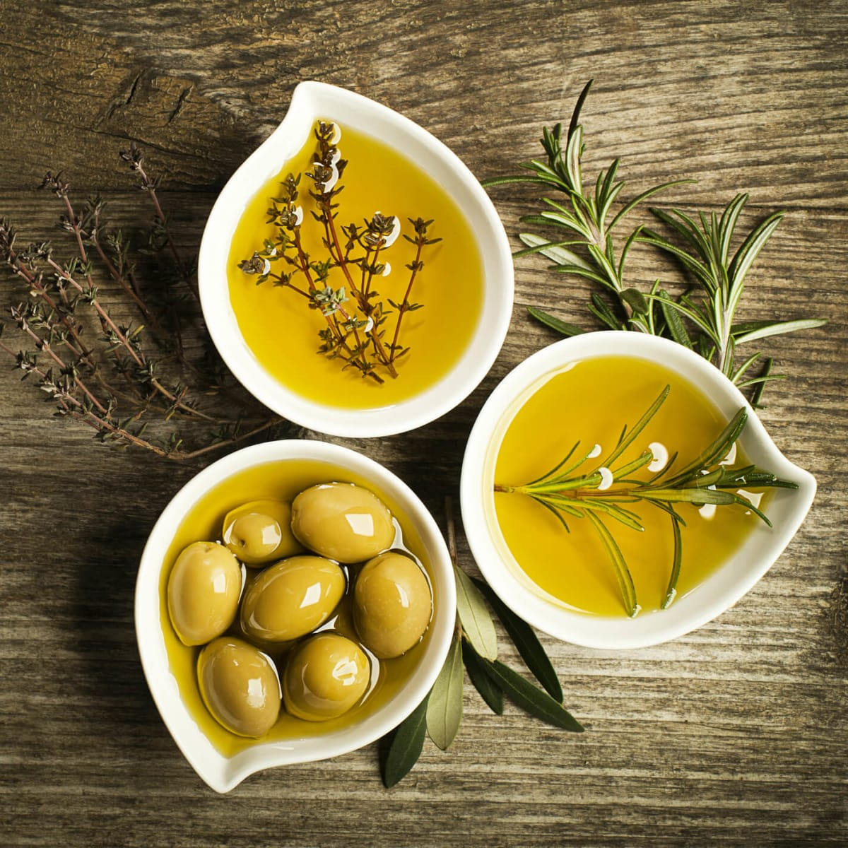 Bowls of olives, olive oil, and herbs