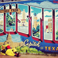Moontower comedy festival's Mother clucker in front of Austin mural