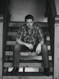 musician John Fullbright sitting on stairs