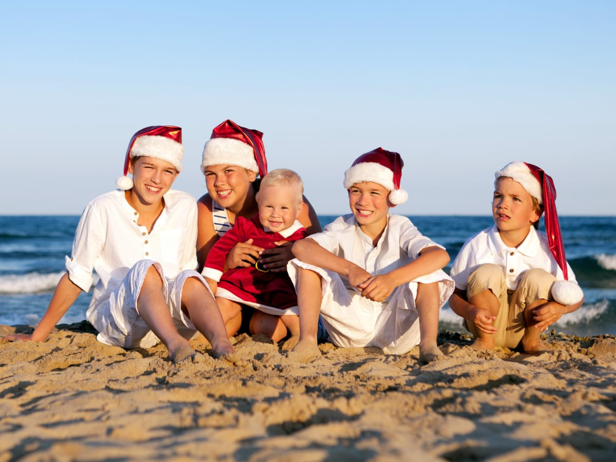 Kids on the beach wearing Santa hats