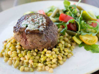 Filet with garlic butter over shell peas at Wayward Sons restaurant in Dallas